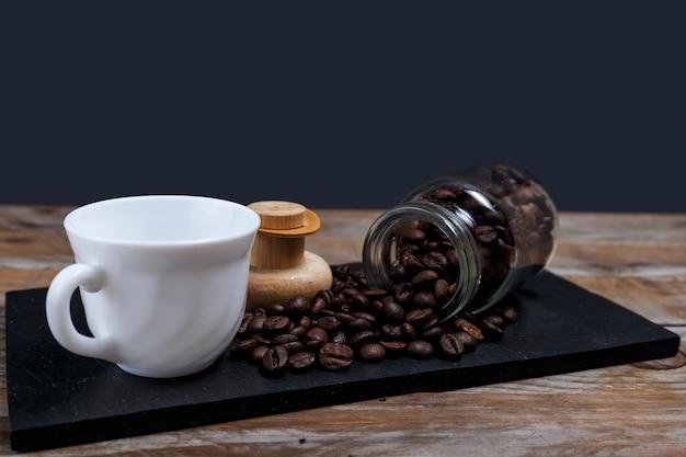 Kaffeebohnen, die aus das glas herauskommen