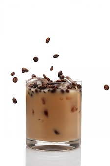 Kaffeebohnen, die in cocktail mit irischem cremelikör in einem glas voll eis fallen.