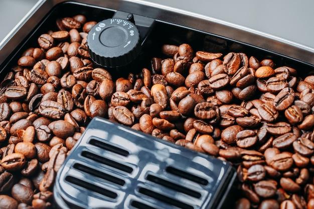Kaffeebohnen, die in einer kaffeemaschinenmühle mahlen