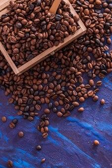 Kaffeebohnen, die von einer holzkiste auf blauen tönen wiederbeleben