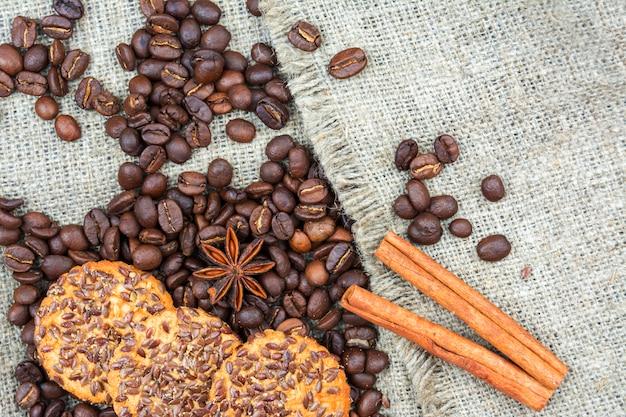 Kaffeebohnen, eine zitronenscheibe, zimtstangen und kekse sind auf dem alten leinenstoff.