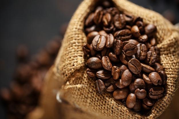 Kaffeebohnen-espresso-nahaufnahme im jutesackbeutel.