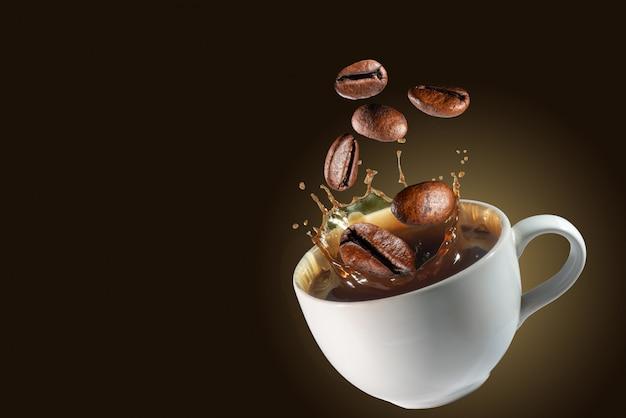 Kaffeebohnen fallen auf spritzkaffeetassenhintergrund