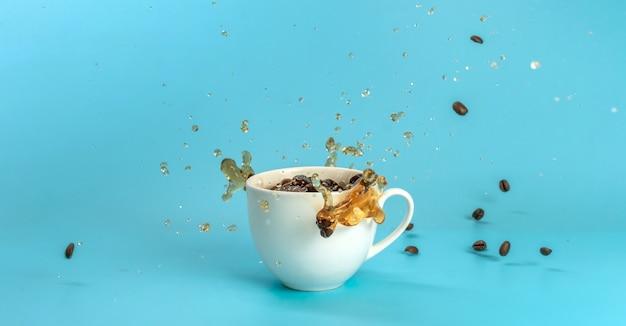 Kaffeebohnen fallen in eine weiße tasse und machen spritzer