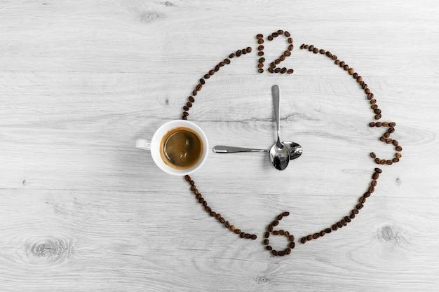 Kaffeebohnen gefaltet in form einer uhr. anstelle der nummer 9 eine tasse kaffee, was bedeutet, dass es zeit ist, kaffee zu trinken
