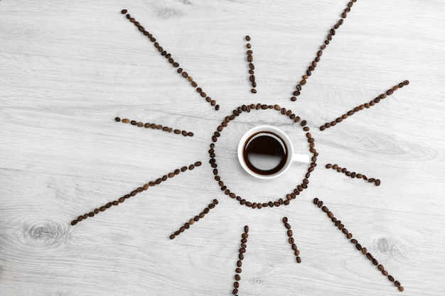 Kaffeebohnen gefaltet in form von der sonne auf einem hölzernen. in der mitte steht eine tasse kaffee, es ist also zeit, nach sonnenaufgang kaffee zu trinken