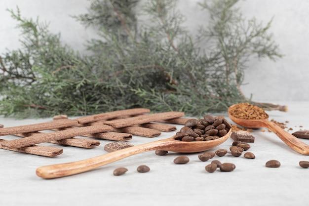 Kaffeebohnen, gemahlener kaffee, kekse und schokolade auf marmoroberfläche