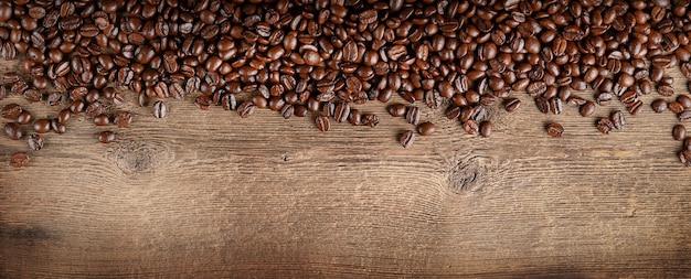 Kaffeebohnen grenzen auf dunklem holzhintergrund. kopieren sie platz, ansicht von oben.