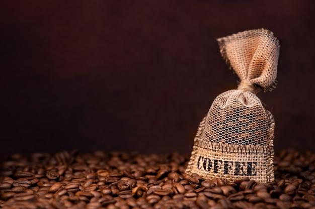 Kaffeebohnen im beutel auf dunklem hintergrund mit kopienraum. frisch geröstete kaffeekörner im leinensack.