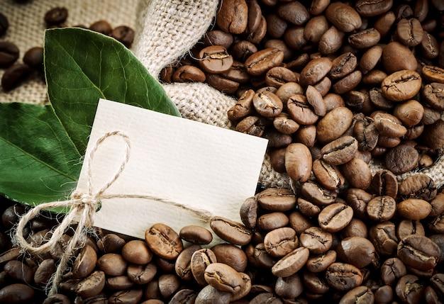 Kaffeebohnen im braunen löffel auf sackleinen.