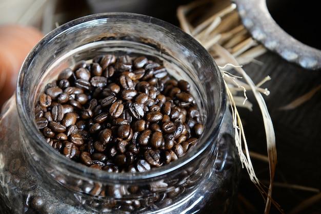 Kaffeebohnen im glasweinleseglas mit holzkiste