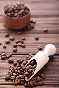 Kaffeebohnen im hölzernen löffel auf braun