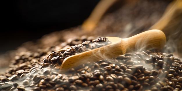 Kaffeebohnen im hölzernen löffel mit rauche auf stapel von kaffeebohnen