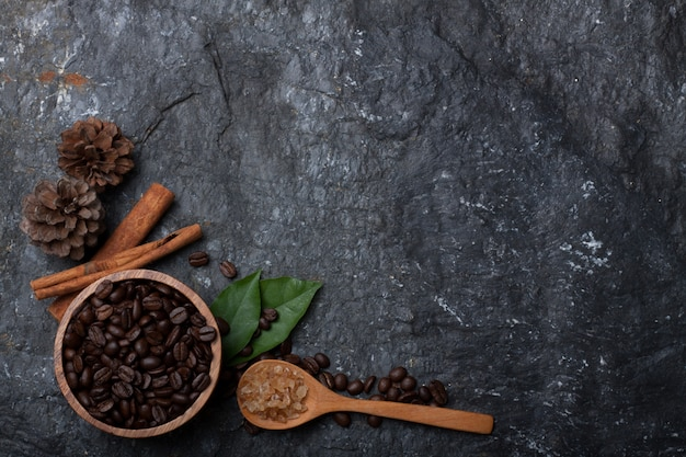 Kaffeebohnen im hölzernen schalen-, kiefern- und grünblattzucker auf hölzernem löffel auf schwarzem steinhintergrund
