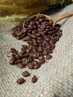 Kaffeebohnen im holzlöffel auf sackleinen