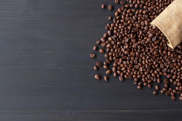 Kaffeebohnen im leinwandsack auf altem hölzernem hintergrund. draufsicht
