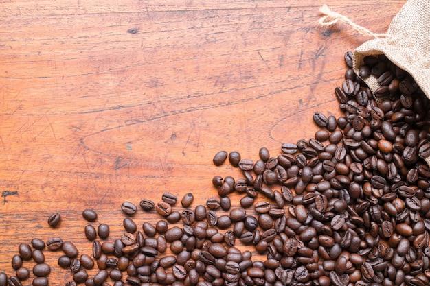 Kaffeebohnen im sack und in den kaffeebohnen auf holztisch mit kopienraum