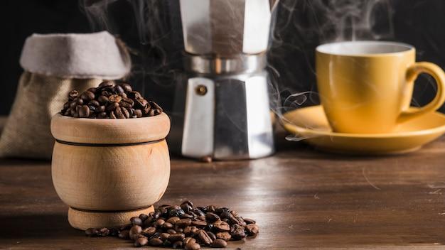 Kaffeebohnen im topf nahe kaffeesatz, sack und kaffeemaschine