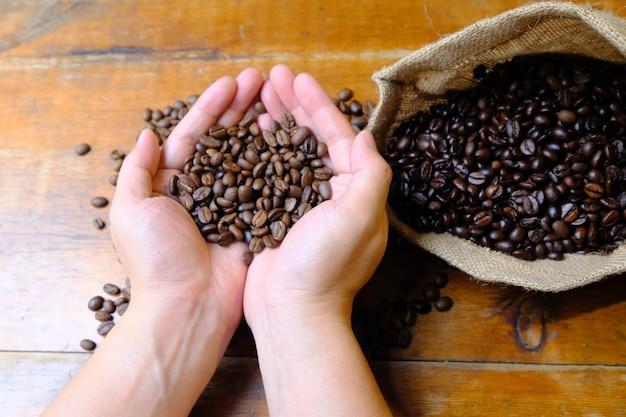 Kaffeebohnen in den händen mit einer kaffeetasche und einer tasse kaffee latte