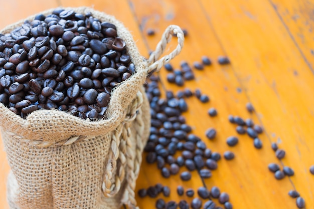 Kaffeebohnen in den säcken auf hölzernen brettern