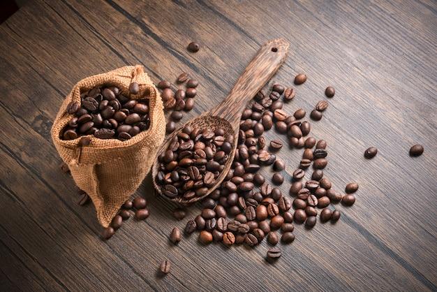 Kaffeebohnen in der hölzernen löffel- und sacktasche des kaffees auf sacktasche auf hölzernem hintergrund