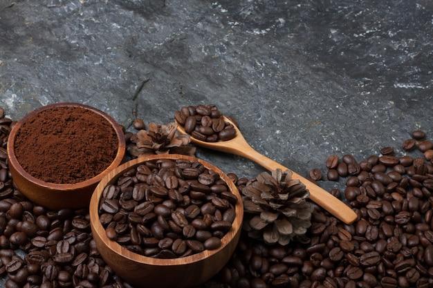 Kaffeebohnen in der hölzernen tasse und in der kiefer, holzlöffel auf schwarzer steinbeschaffenheit
