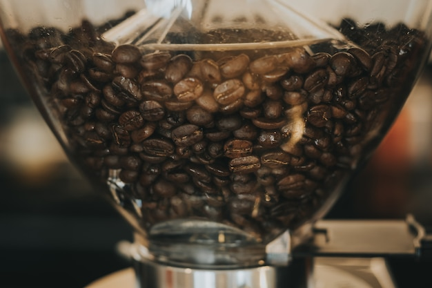 Kaffeebohnen in der kaffeemaschine mit weinlesefarbton.