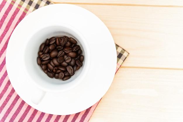 Kaffeebohnen in der weißen schale, gewebe plaid auf einem holztisch.