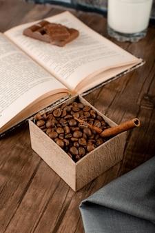 Kaffeebohnen in einem karton und einem buch