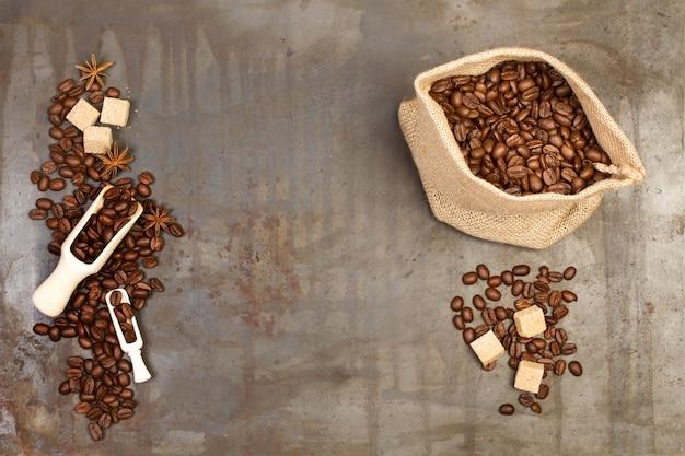 Kaffeebohnen in einem leinensack und auf einem rostigen metalltisch in einer draufsicht