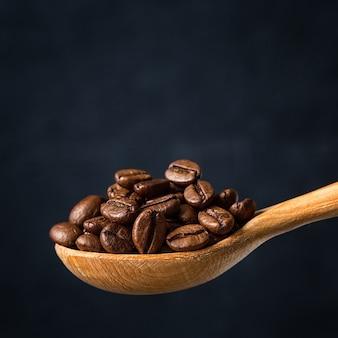 Kaffeebohnen in einem löffel auf grau