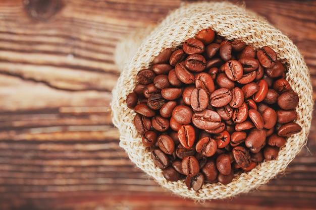 Kaffeebohnen in einem sack auf einer holzoberfläche weicher kontrast aromatische geröstete kaffeebohnen