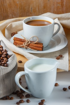 Kaffeebohnen in einem sack, milch, trockenem zimt und einer tasse kaffee auf einer plattform und einem weißen tisch. seitenansicht.
