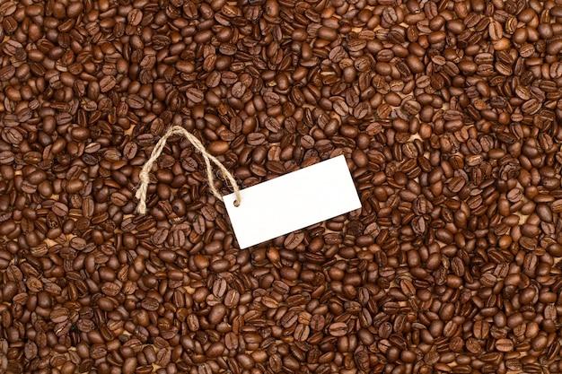 Kaffeebohnen in einer draufsicht mit einem leeren weißen etikett
