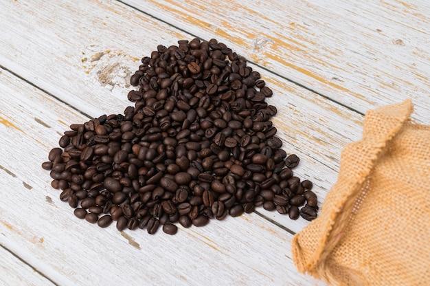 Kaffeebohnen in einer herzform angeordnet. lieben sie, kaffee zu trinken
