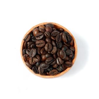 Kaffeebohnen in einer holzschale isoliert auf weißem hintergrund, ansicht von oben