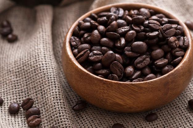 Kaffeebohnen in einer holzschale.