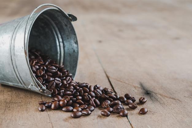Kaffeebohnen in einer metallwanne auf bretterboden