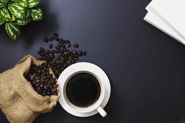 Kaffeebohnen in einer sacktasche und in einem schwarzen kaffee in einer weißen kaffeetasse, bäume, bücher auf einem schwarzen hintergrund