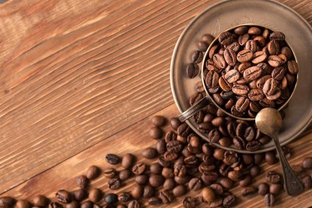 Kaffeebohnen in einer silbernen schale auf holztisch