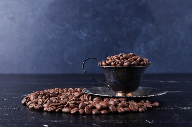 Kaffeebohnen in einer tasse und auf dem schwarzen