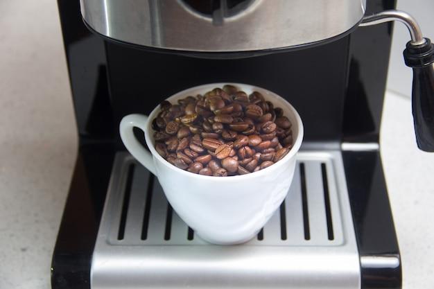 Kaffeebohnen in einer weißen tasse. zubereitung von kaffee. kaffeemaschine