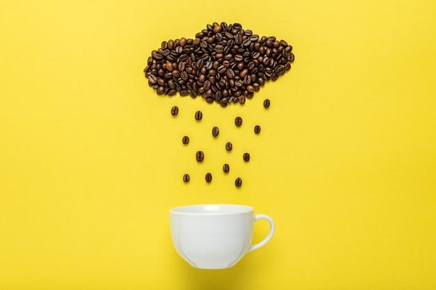 Kaffeebohnen in form einer regnerischen wolke mit weißer tasse auf gelb.