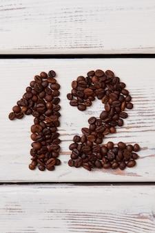Kaffeebohnen in form von nummer zwölf auf weißer oberfläche. braune geröstete samen auf holzbohlen, die 12-nummer bilden.