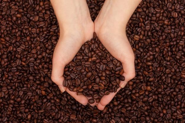 Kaffeebohnen in frauenhänden auf kaffeebohnenhintergrund