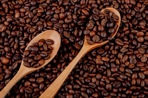 Kaffeebohnen in hölzernen löffeln auf kaffeebohnen-draufsichthintergrund