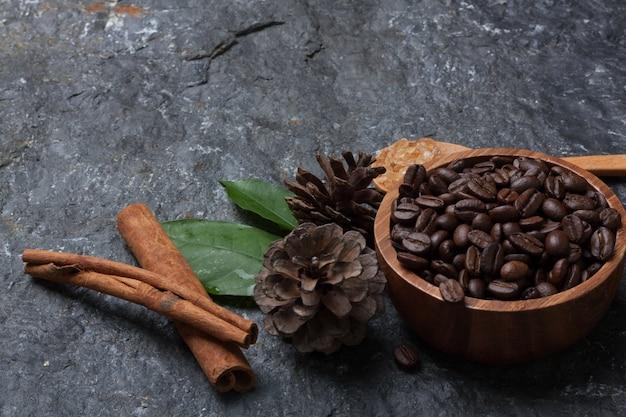 Kaffeebohnen in holztasse, zucker in holzlöffel kiefer und blatt auf schwarzem stein