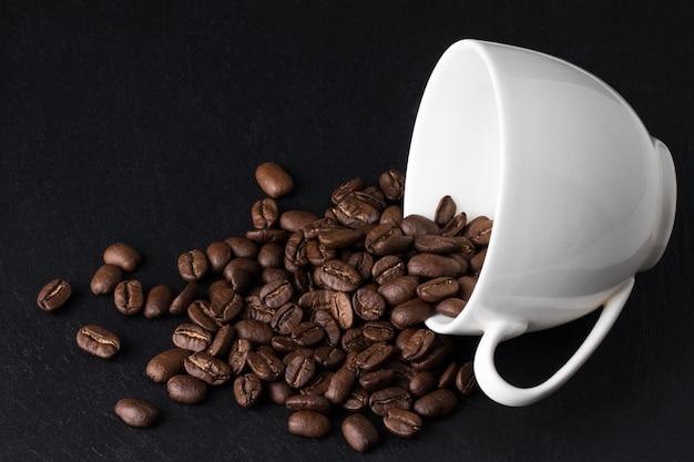 Kaffeebohnen in kaffeetasse auf dunkel