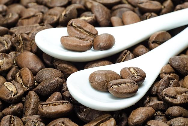 Kaffeebohnen in keramiklöffeln auf geröstetem kaffeehintergrund