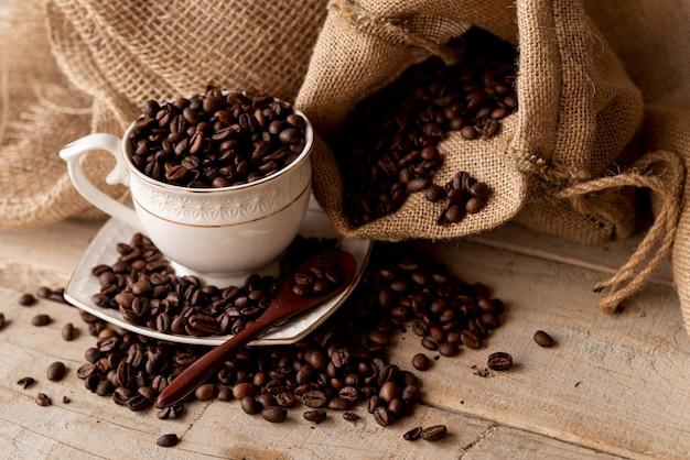 Kaffeebohnen in tasse und leinwandsäcken